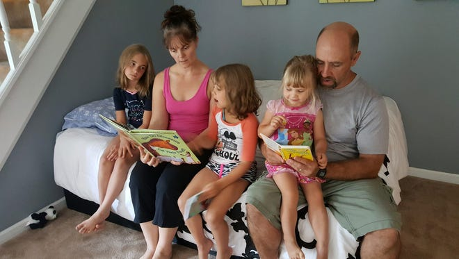 Breast cancer survivor Shawna Gruca and her husband John of Clarkston read to daughters (from left) Carley, 8, Jacklynn, 5, and Ashley, 2, in this photo taken Wednesday, Aug. 9, 2017. The family was awarded a $6,000 wish from Brighton-based charity Fund A Life Foundation.