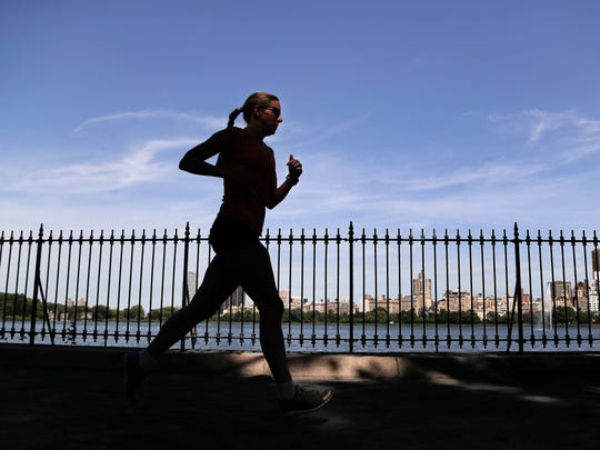 FILE - This Aug. 9, 2016 file photo shows a woman jogging through Central Park in New York. The park serves as a collective backyard for New York City residents who live in tiny apartments. It's also one of the city's greatest free attractions for visitors.