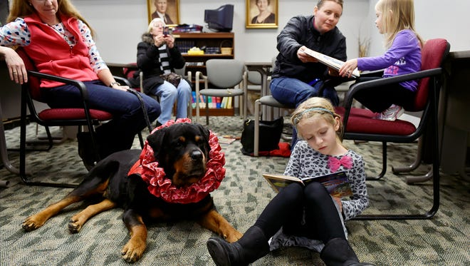 Kelly Skiptunas, 52, of Lower Windsor Township, far left, and her therapy dog, Spencer, listen as Emily Gordon, 6 of Springettsbury Township, reads aloud. Her grandmother, Janet Smeltzer, second from left, observed. At the same time, Emily's mother, Becky, helped her sister, Leah, 2, pick a book.