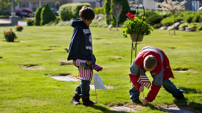 Airrion Hinojosa, 9, of Port Huron, and Garrison Smith, 10, of Marysville, place flags at the graves of veterans along with members of American Legion Post 449 on Saturday at Riverlawn Cemetery in Marysville.