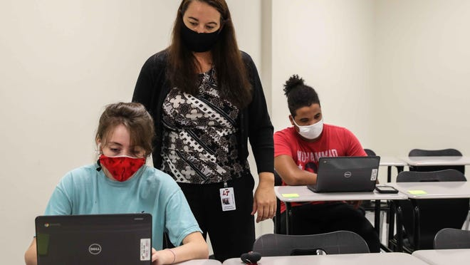 Substitute teacher Bernadette Martens-Saxelby monitors students Mikaela Kuentz and Akaris Smith in her classroom Wednesday while they attend an online class at Lake Travis High School.