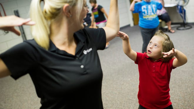Dance instructor Natalie Rascher, of Evansville, dances with Mary Gries, 8, also of Evansville, during SMILE on Down Syndrome's summer dance class at  the Deaconess Health Science Building Wednesday. Dancers are preparing for their Summer recital.