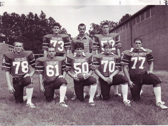Teurlings Catholic assistant coach Tommy Badon with Rebels' offensive line prior to the undefeated, unscored upon regular season of 1982. The line includes Brian Racca (73), Kelvin Thibodeaux (52), Chad Habetz (78), Joe Ashy (61), Cecil Lotief (50), Kevin Boudreaux (70) and Jay Hebert (77).