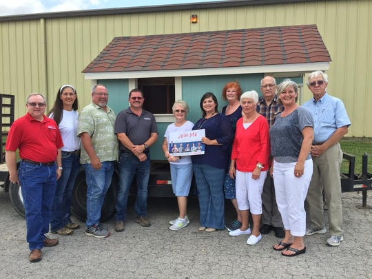 CASA receives a playhouse from the Twin Lakes Home Builders Association Thursday. The agency will raffle the playhouse at the Baxter County Christmas Parade.