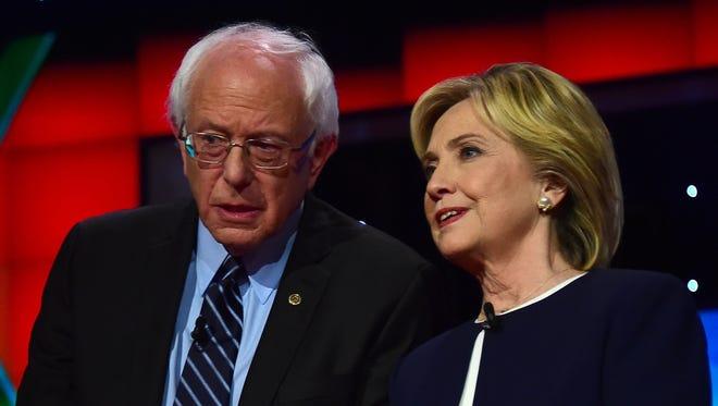 Presidential hopeful Bernie Sanders speaks with Hillary Clinton during the first Democratic presidential debate in Las Vegas on Oct. 13.