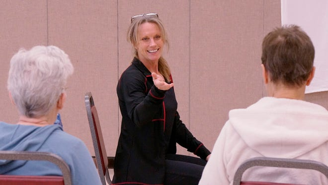 Instructor Bonnie Holben talks posture. Back away from the chair, stomach in, and shoulders back.