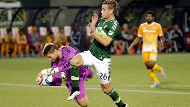 Houston Dynamo goalkeeper Tyler Deric, left, makes a diving save against Portland Timbers midfielder George Fochive during the first half of an MLS soccer game in Portland, Ore., Friday, Aug. 21, 2015.