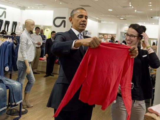 US President Barack Obama holds up a shirt as he shops for clothing for his family alongside store employee Susan Panariello (R) during a visit to a Gap clothing store in New York City, March 11, 2014, to highlight his proposal to raise the federal minimum wage. AFP PHOTO / Saul LOEBSAUL LOEB/AFP/Getty Images