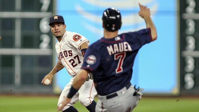 Minnesota Twins designated hitter Joe Mauer (7) is out at second base as Houston Astros second baseman Jose Altuve (27) throws to first base during the fifth inning Wednesday at Minute Maid Park in Houston.