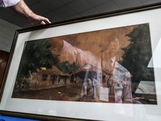 Appraiser Aaron Bastian is reflected in a print during the traveling Antiques Roadshow event.