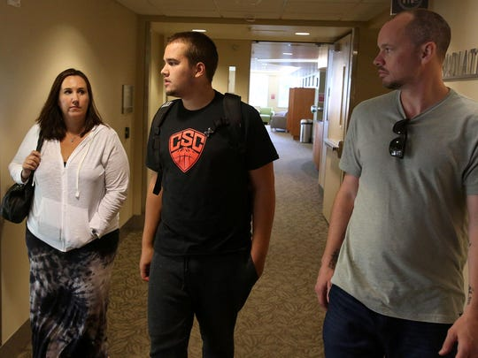 Kyle Atkinson, center, and his mother, Holley Oglesby, and friend and former coach Mike McShane leave after Atkinson's fourth day of radiation therapy treatment at Oregon Health and Science University on Thursday, July 2, 2015, in Salem, Ore.