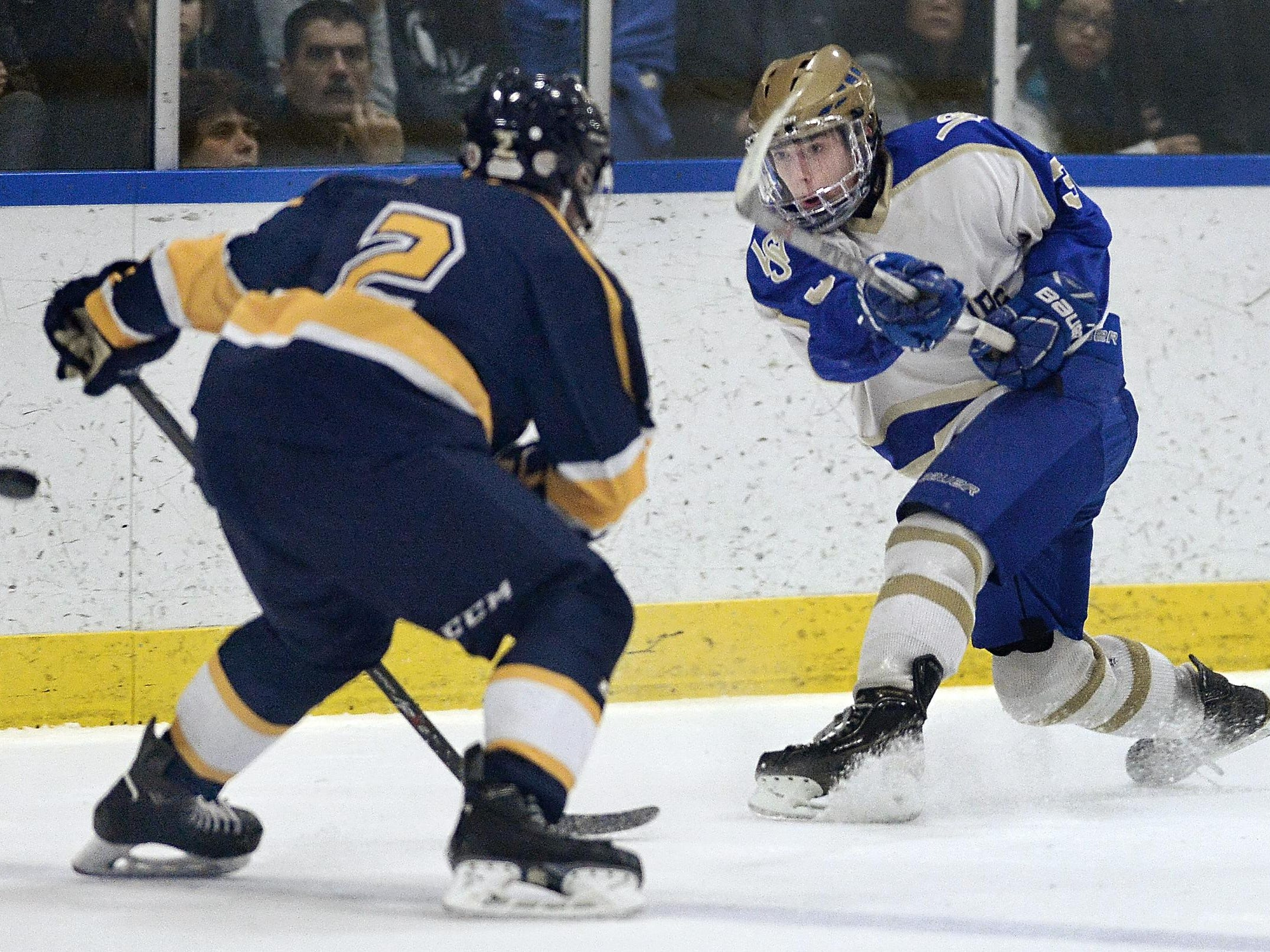 Webster Schroeder's Tommy Winn, right, takes a shot on goal past Webster Thomas defender Zachary Fosdick during regular season game played at Webster Ice Arean as part of the Robert J. Smith Memorial High School Hockey Showcase on Saturday, January 9, 2016. Webster Schroeder and Webster Thomas played to a 2-2 tie.