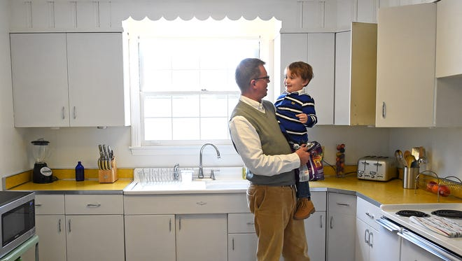 Robbie Jones of Madison holds his godson, Camdon Langford, 3, as they search the kitchen for some snacks. Jones recently bought a 1950s ranch in original condition. He wrote a letter to the sellers promising to preserve the home's original character, including the kitchen.