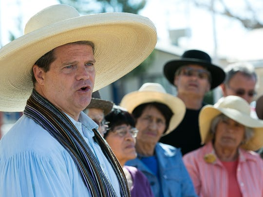 Rev. Jeff Sutton wear one of Miguel Silva's hats on Tuesday as he speaks to friends and family during the unveiling of a memorial in Silva's honor at Klein Park.