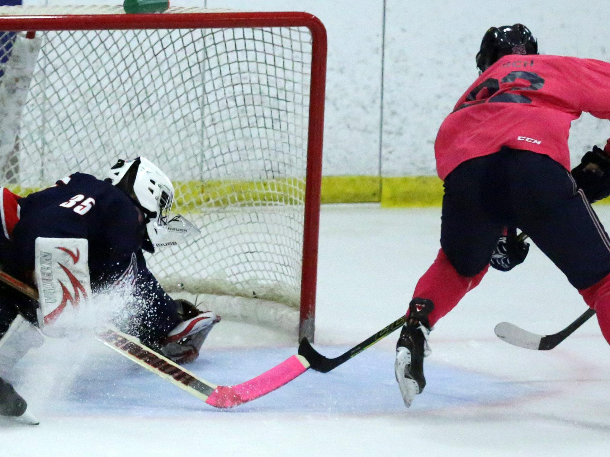 Trenton Bliss of Appleton United gets the puck past Nathan DeLisle of the Fox Cities Stars in a Badgerland Conference boys' hockey game Tuesday at the Appleton Family Ice Center.