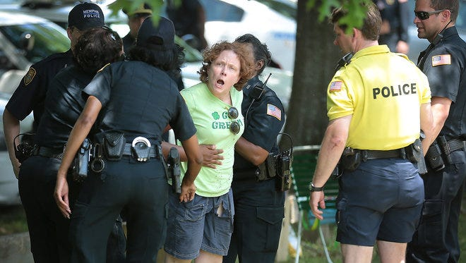 Maureen Spain is arrested by Memphis officers during an act of civil disobedience at Overton Park. A crowd of protesters gathered in opposition to the continued use of the Greensward by the Memphis Zoo for overflow parking where two people were arrested.