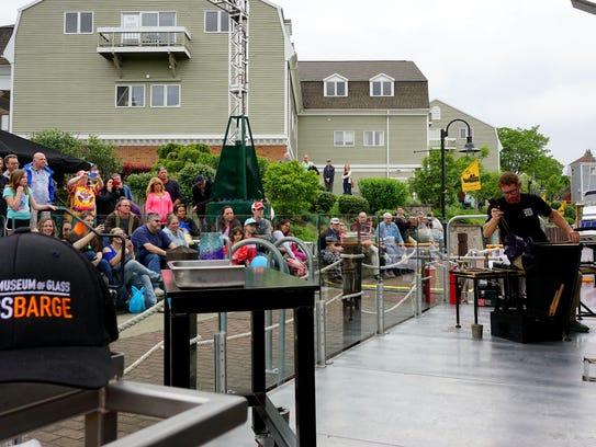 Spectators at Fairport Canal Days watch a hot glass