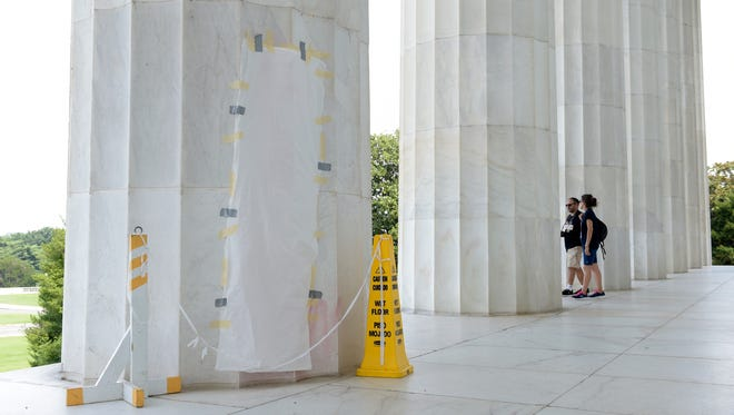 Graffiti scrawled on a column of the Lincoln Memorial is covered up in Washington, Wednesday, Aug. 16, 2017. The National Park Service said someone used red spray paint to scrawl an anti-law message on the Lincoln Memorial in Washington.