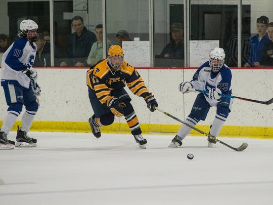 Salem players Marty Mills (No. 11) and Martino Zaia (No. 25) converge on Trenton puck carrier Devin Dunn (No. 17) during Friday's hockey game at Plymouth Cultural Center.