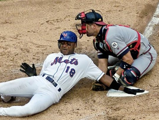 FILE - In this June 23, 2001, file photo, New York Mets' Darryl Hamilton is tagged out at home plate by Atlanta Braves catcher Javy Lopez during the third inning of a baseball game at Shea Stadium in New York.
