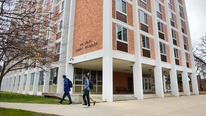 Students walk past the W.W. Holes Hall dormitory high rise building Wednesday at St. Cloud State University. SCSU is planning to demolish Holes Hall in the next couple years as it's a highly underutilized space, President Potter says.