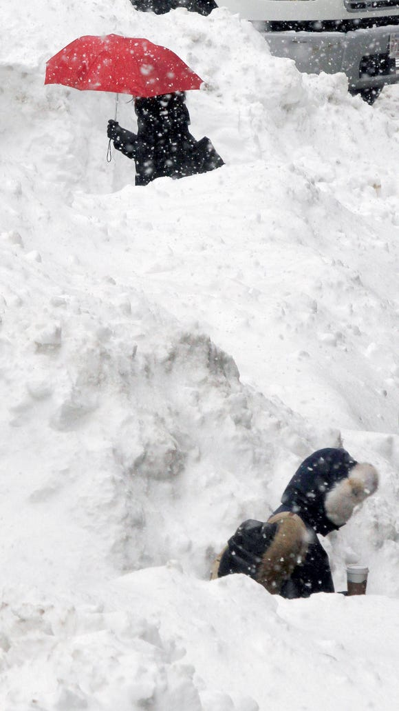 Commuters walk between piles of snow on a street in