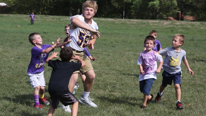 Indianola High School junior Colt Carpenter gets rid of the ball during a recess game of keep-away at Whittier Elementary on Sept. 22. The high school students visited the elementary as part of homecoming week celebrations.