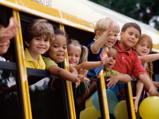 Group of students looking out of a school bus