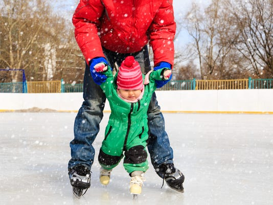 father and child learning to skate in winter