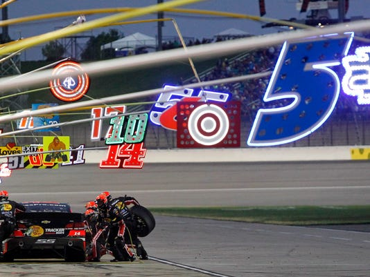 NASCAR driver Tony Stewart (14) pits under lighted team signs during a Sprint Cup Series auto race at Kansas Speedway in Kansas City, Kan., Saturday, May 9, 2015. (AP Photo/Colin E. Braley)