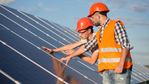 Construction workers examine solar panels.