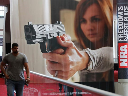 A attendee passes by a large banner advertising a handgun during the NRA convention at the Georgia World Congress Center on Thursday, April 27, 2017, in Atlanta.