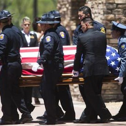 The casket of Officer Jair Cabrera is carried to a