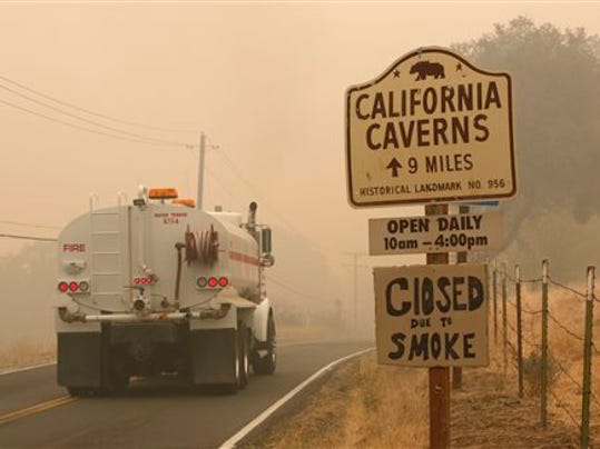 A water truck passes a warning sign that the California Caverns historic site is closed due to smoke from the Butte Fire, Saturday, Sept. 12, 2015, near San Andreas, Calif. Firefighters gained some ground Saturday against the explosive wildfire that incinerated buildings and chased hundreds of people from mountain communities in drought-stricken Northern California. (AP Photo/Rich Pedroncelli)