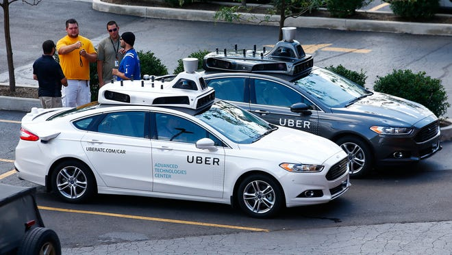 Uber employees stand by self-driving Ford Fusion hybrid cars while test driving the vehicles, Thursday, Aug. 18, 2016, in Pittsburgh. Uber said that passengers in Pittsburgh will be able to summon rides in self-driving cars with the touch of a smartphone button in the next several weeks. The high-tech ride-hailing company said that an unspecified number of autonomous Ford Fusions with human backup drivers will pick up passengers just like normal Uber vehicles. Riders will be able to opt in if they want a self-driving car, and rides will be free to those willing to do it, spokesman Matt Kallman said.