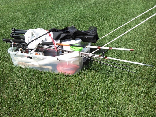 Jeff Kiebel, who preferred not to be photographed, pulls all of his fishing gear along in this simple plastic sled.  It holds a folding chair, tackle boxes, fishing rods, bait and more secured with bungee cords.