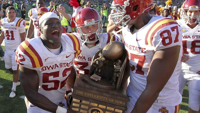 Iowa State players, from left, Jeremiah George, Jeff Woody and David Irving carry the Iowa Corn CyHawk Series trophy from the field after Iowa State defeated Iowa 9-6 in an NCAA college football game Saturday, Sept. 8, 2012, in Iowa City, Iowa.