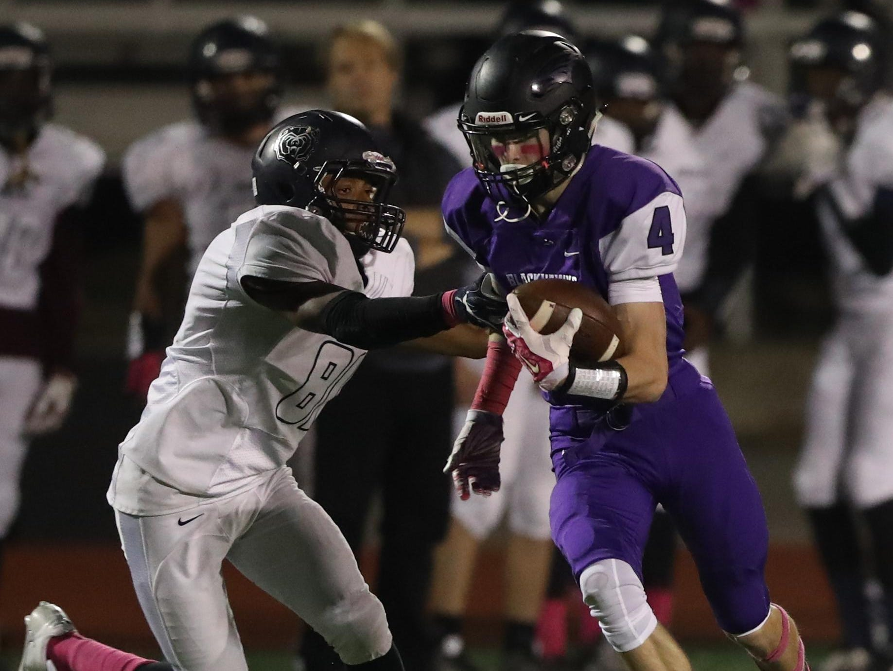 Bloomfield Hills' Ty Slazinski tries to elude a Berkley defender after catching a pass in Friday night's game.