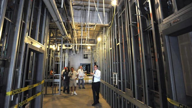 In this 2016 file photo, a hospital executive and a member of the Office of Statewide Health Planning and Development Office tours the unfinished tower project.