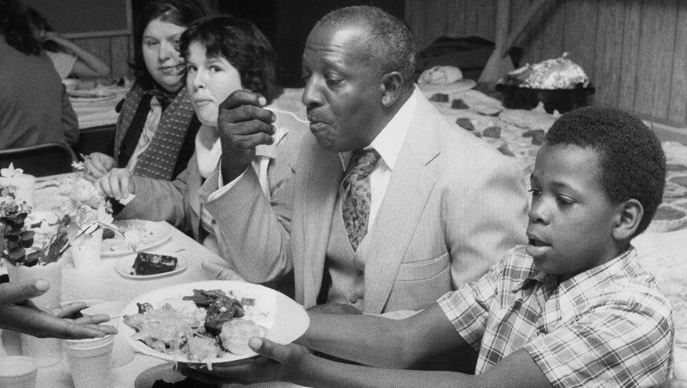 Steve Brakens takes a plate of food at a 1983 Thanksgiving