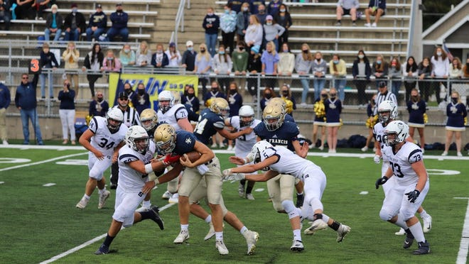 Sault High's Daylan Lujan (59) and John Robinson (5) corral a Traverse City St. Francis runner during last week's season opener. The Blue Devils go on the road again this Friday night at Marquette.