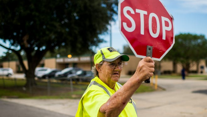 Barbara Breaux, a crossing guard of 39 years, holds a stop sign while guiding student walkers during afternoon dismissal at Duson Elementary School in Duson, La., Thursday, Oct. 1, 2015.