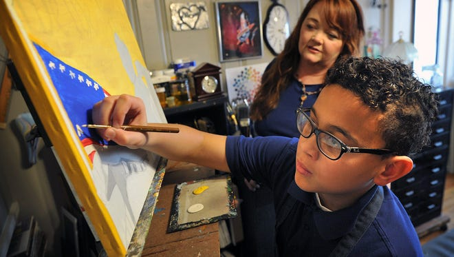 Crockett Elementary fifth grader Trae Steele works on his latest painting with a little supervision from his artist grandmother Marsha Wright Reeves. Steele is selling his artwork at the After Hours Artwalk Thursday at the Wichita Falls Art Association gallery. He is raising money for a school trip to Washington D.C.