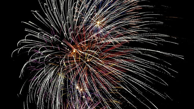 Fireworks light up the sky as the wind stretches their shapes Saturday night during Garden City's annual fireworks display originating in the Arkansas River bed area. Garden City was one of the communities in southwest Kansas to hold a display on July 4.