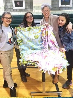 "Participants show off one of the blankets created during the ""Make-A-Blanket Day"" held on Feb. 16 by the Applied Math and Science Academy at Veterans Memorial School in Vineland."