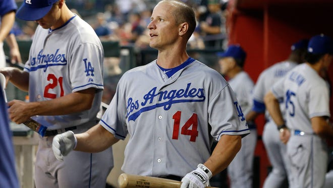 Los Angeles Dodgers' Mark Ellis talks with a teammate in the dugout prior to a baseball game against the Arizona Diamondbacks on Monday, Sept. 16, 2013, in Phoenix.