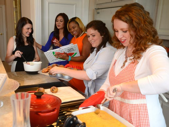"""Ann Novakowski takes blueberry orange muffins out of the pan and Laura Griffin dishes out cheese grits while Mallory Coats stirs batter and Jayde Herman and Tori Woods look through the Junior League of Pensacola Florida's cookbook """"Some Like it South!""""."""