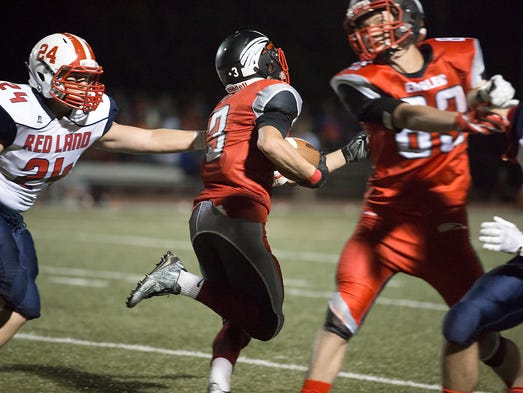 Dover's Derek Arevalo breaks an arm tackle by Red Land's