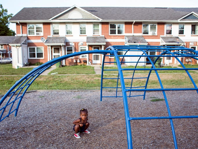 Summer-June Peak, 2, sits under the climbing gym at the playground at Hillcrest Apartments in Asheville, Wednesday, July 16, 2014. Summer-June's mom, Darrian Waters, said she used to live at Hillcrest about 10 years ago and still has a lot of friends and family there. Hillcrest is one of the communities in the Asheville Housing Authority potentially going through an overhaul to transition from public housing into Section 8. 7/16/14