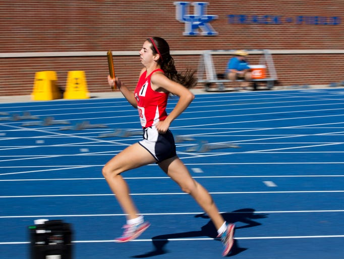 Taylor Connett carries the baton as St. Henry wins the 4x800 meter relay.